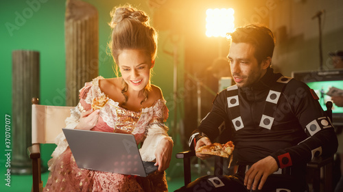 Beautiful Smiling Actress Wearing Renaissance Dress and Actor Wearing Motion Capture Suit having Lunch Break, Sitting on Chairs, Use Laptop and Talk Fototapete