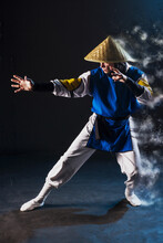 Cosplay Shaolin Monk In A Straw Hat Stands In A Fighting Stance Hand Extended Forward With The Effect Of Scattering In The Air On A Black Background And With Smoke