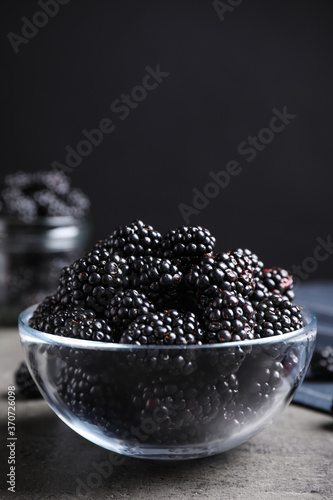 Fotografering Delicious fresh ripe blackberries in glass bowl on grey table
