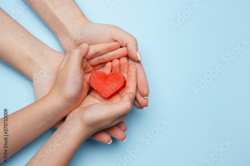 Fototapeta Human hands holding, giving heart isolated on blue background with copyspace. Concept of emotions, feelings, charity, family, supporting hand. Thankful, inspirational. Romantic and togetherness. obraz