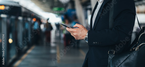 Photo Man hands holding phone at train station stock photo