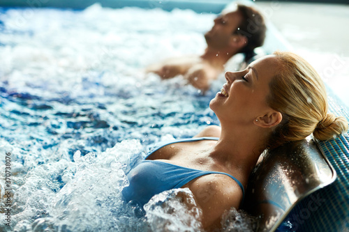 Obraz Relaxed woman enjoying in water massage at thermal pool. - fototapety do salonu
