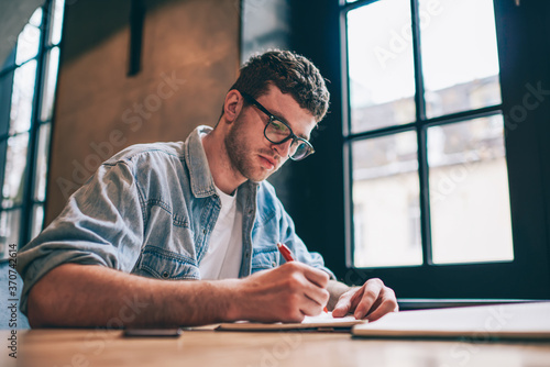 Photo Serious male student writing essay sitting at desktop and spending time for cour