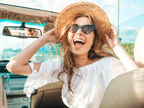 Obraz Portrait of young beautiful and smiling hipster girl in convertible car. Sexy carefree woman driving cabriolet. Positive model riding and having fun in sunglasses and hat - fototapety do salonu
