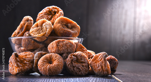 Cuadros en Lienzo Composition with bowl of dried figs on wooden table