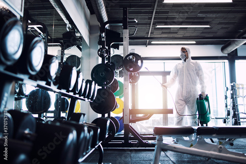 Fototapeta premium Gym disinfection and healthcare. Man in white protection suit disinfecting and fitness equipment and weights to stop spreading highly contagious coronavirus or COVID-19.