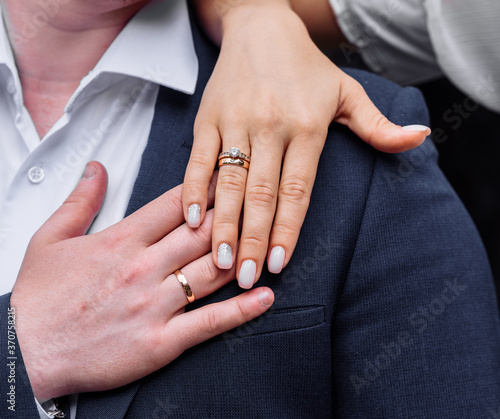 Canvastavla young people with twisted hands on which wedding engagement rings in white gold with diamonds