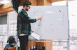 canvas print picture - Professional male coach dressed in casual wear pointing on flip chart with graphics conducting training workshop in office.Creative teacher explaining studying material during lesson in college