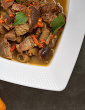 Partial View Of A Bowl Of Hot Spicy Nigerian Goat Meat Pepper Soup. Served In A White Bowl On A Dark Table