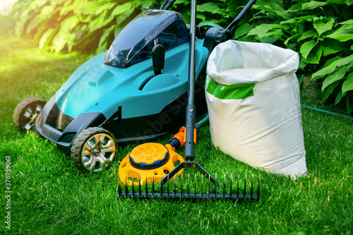 Photo gardening tools and lawn care equipment on green grass