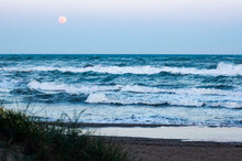 Beach With Wild Sea With Rising Full Moon In Background, Focus On Moon And Sea, Blurry Foreground