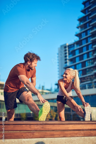Obraz Young adult sporty couple working out outdoors. - fototapety do salonu