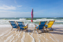 Four Empty Beach Chairs Being Overtaken By Incoming Tide