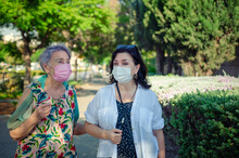 Caregiver And The Old Lady Have A Lively Conversation As They Walk. Both Are Wearing Protective Masks During The Coronavirus.