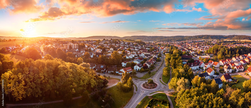 Fototapeta Aerial panorama of a European town at sunrise, with magnificent colorful sky and warm light