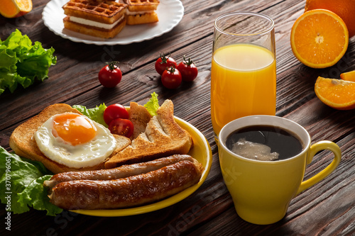 Fried egg on roasted toast with sausage, fresh leaf lettuce and cherry tomato on yellow plate. Coffee, juice on glass cup, waffles and slices of orange on wooden background. American breakfast concept © Gleb