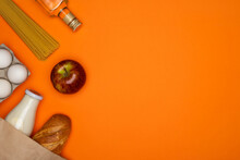 Bread And Bottle Of Milk In Paper Bag. Spaghetti, Sunflower Oil, Eggs And Red Apple On Orange Background. Healthy Food, Delivery, Donation Concept. Food Stock For Quarantine. Top View, Copy Space