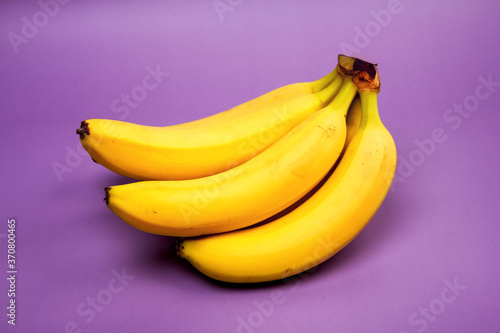 Fotografie, Obraz bunch of bananas on a purple background