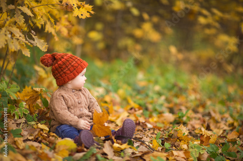baby in knitted hat and jacket sits on grass in Park against background of autumn trees Wallpaper Mural