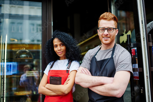Fotografie, Tablou Portrait of prosperous team of two multicultural professional barista and waitre