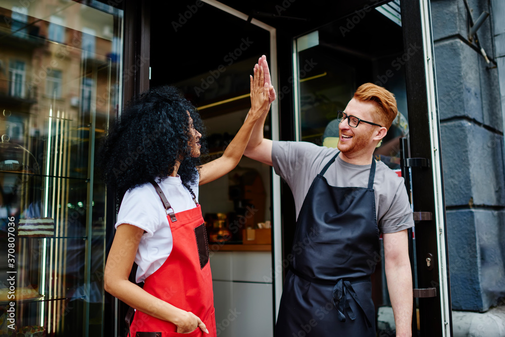 Fototapeta Satisfied multiethnic small business owners giving high five gesture at entry of cafe