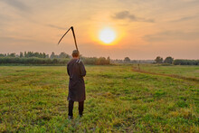 An Senior Muslim Man In A Skullcap And Traditional Clothes Leaves With A Hand Scythe From The Hay Field At Sunset.