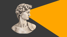 Head Of An Antique Statue On A Gray Background With An Orange Triangle In Front