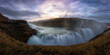 Breathtaking view of huge waterfall with rapid flow against cloudy sky during sunset