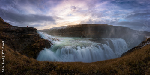 Breathtaking view of huge waterfall with rapid flow against cloudy sky during sunset - 370829669