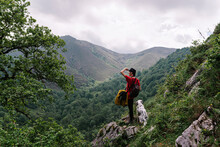 Back View Female Tourist Doing Hiking In Countryside And Admiring Scenery Of Mountainous Valley With English Setter Dog