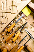 Top View Of Set Of Various Chisels For Wood Carving Placed On Messy Workbench With Wood Shavings