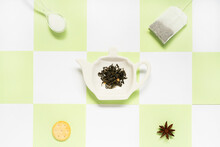Top View Of Ceramic Plate In Form Of Teapot With Green Tea Leaves Near Transparent Tea Bag With Spoon Of Sugar And Salty Cracker With Dry Anise