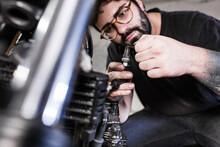 Serious Male Mechanic Repairing Dirty Spark Plug Of Motorbike While Working In Garage