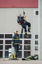 Brave Fireman Climbing Rope Un...