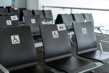 Rows Of Empty Black Seats In Public Waiting Area For People With Physical Disabilities And People With Special Needs With Square White Sign Demonstrating Person On Wheelchair