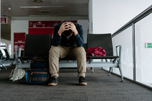 Full Length Faceless Depressed Exhausted Male Traveler In Casual Wear Sitting On Seats With Head In Hands In Modern Airport Departures Waiting Area
