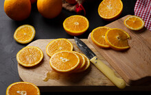 From Above Composition Of Halves Of Fresh Oranges On Wooden Boards And Mesh Bag Near Glass Jar With Orange Custard And Plastic Squeezer