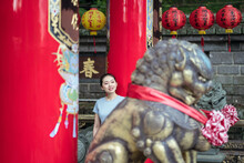 Positive Smiling Asian Lady In Casual Shirt Leaning On Column While Spending Sunny Day In Traditional Buddhist Religion Temple Against Monument Of Lion In Taipei
