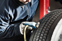 Crop Male Master In Protective Uniform Using Tire Regroover While Working In Garage