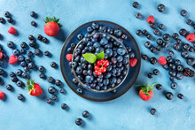 Fresh Blueberries, Red Currants And Strawberries With Green Leaves, Shot From Above