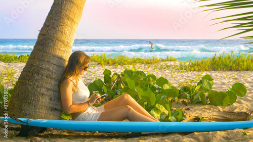 Fotografía CLOSE UP: Woman on surfing trip in Barbados surfs on internet instead of ocean