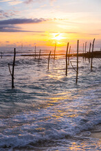 Picturesque Seascape With Wooden Sticks For Traditional Fishing Placed In Water On Background Of Colorful Sundown