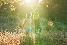 Ten-year-old Boy And Girl Friends Walking Through The Countryside On A Sunny Summer Day In T-shirts And Jeans