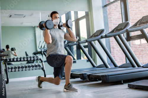 Canvas Print Male athlete wearing face mask while exercising with hand weights in lunge position in a gym
