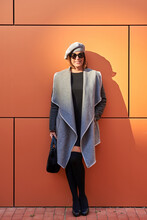 Happy Female In Elegant Wear Leaning On Orange Wall On The Street And Looking At Camera With Sunglasses In Sunny Day