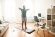 Healthy life. Full length shot of male fitness instructor showing exercises with resistance band while streaming, broadcasting video lesson on training at home using laptop
