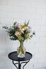 Beautiful Bouquet With Various Flowers In Ornamental Glass Pot Placed On Small Table Against White Brick Wall In Creative Floristry Studio