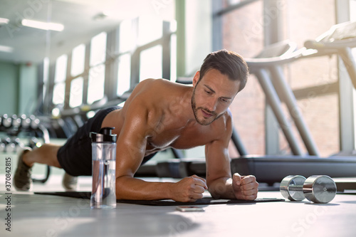 Tela Male athlete in plank pose exercising strength during sports training in a gym