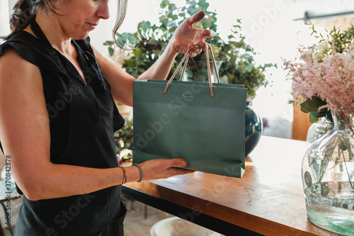 Fotografering Side view of unrecognizable female florist in apron holding paper bag with potte