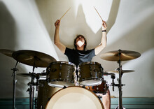 From Below Calm Casual Male Drummer Playing On Drum Kit Sitting On Stage In Shadows